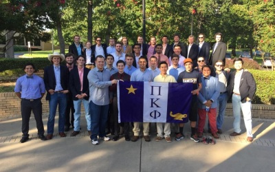 The brothers and new members of the Theta Pi Chapter stand for a picture together at the Riter Bell Tower on the campus of UT Tyler